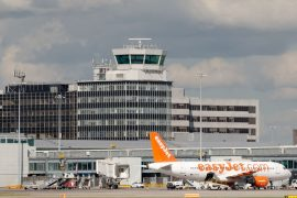 Manchester, United Kingdom - August 27, 2015: Manchester Airport Terminal and easyJet Airbus A319 passenger plane parked. Air control tower on the background.