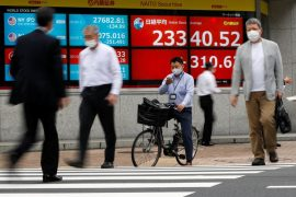 © Reuters. FILE PHOTO: Passersby wearing protective face masks walk past a screen displaying Nikkei share average and world stock indexes, amid the coronavirus disease (COVID-19) outbreak, in Tokyo
