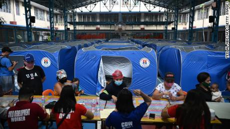 As Connie moves toward the Philippine capital, residents are booking into a makeshift shelter during the evacuation of illegal immigrants living in coastal areas in Manila on Sunday.