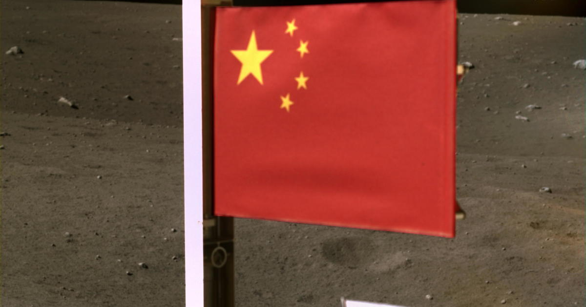 China releases its flag to the moon as a spacecraft carrying lunar rocks is thrown away