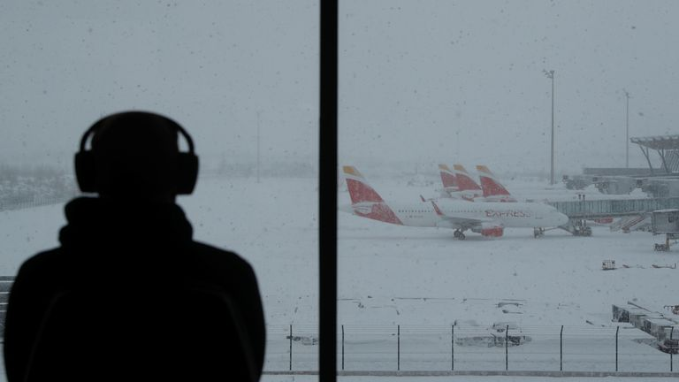 A person watches planes parked at Adolfo Suarez Barajas Airport, which suspends flights due to heavy snowfall.