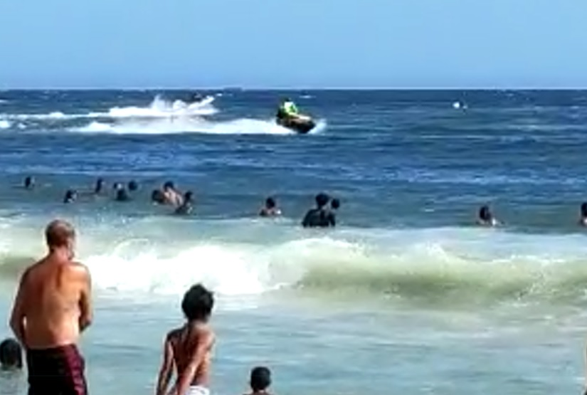 Speed boats and jet skis compete for space with swimmers in Ponta Negra