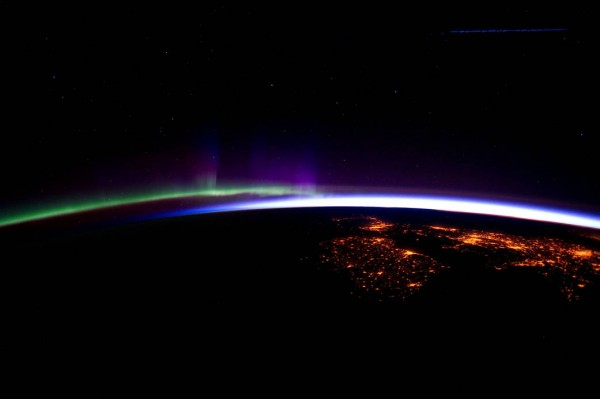Bright arcs of green, purple, and white light against the orange lights scattered across a dark surface.