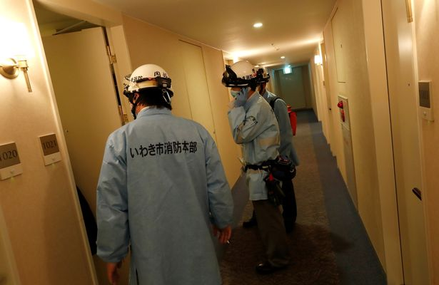 Ambulance crew members stand in the corridor of the hotel where a man was injured in the earthquake