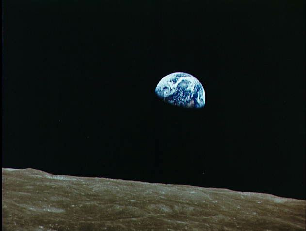 The surface of the moon is below and the blue-green side of the Earth floats above it.