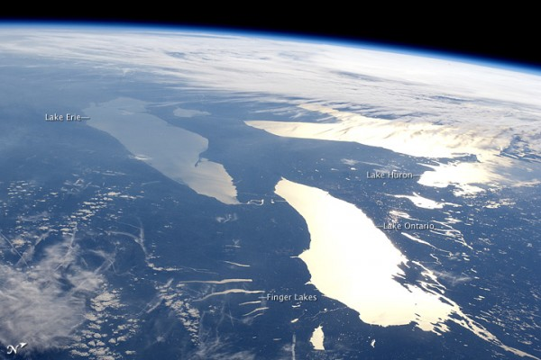 The curve of the Earth with cloudy places, three large, bright, flat areas and lakes.