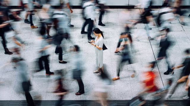 A person is checking his phone among several people walking.